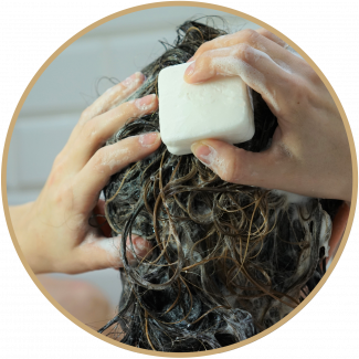 Female washing hair in shower using shampoo bar