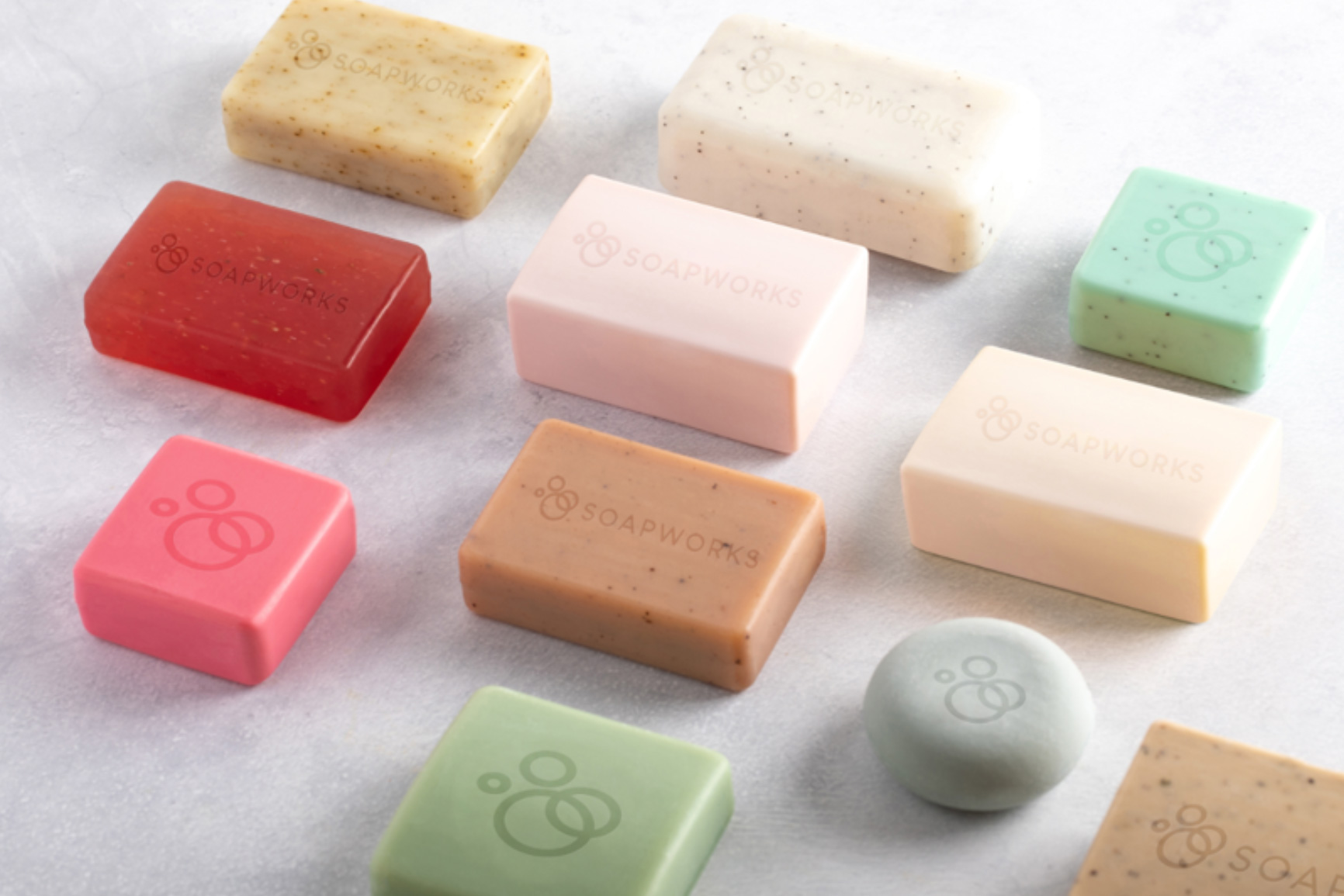 Wide selection of different coloured soaps laid out flat on a neutral background